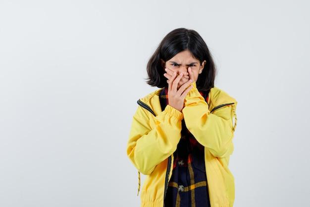 Menina de camisa xadrez, jaqueta de mãos dadas na boca e olhando espantada, vista frontal.