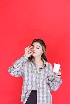 Menina de camisa xadrez segurando uma xícara de café descartável branca e apreciando o sabor