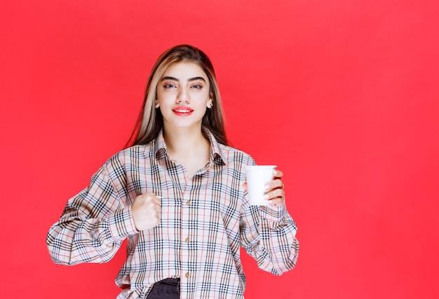 Menina de camisa xadrez segurando uma xícara de café descartável branca e mostrando seu poder