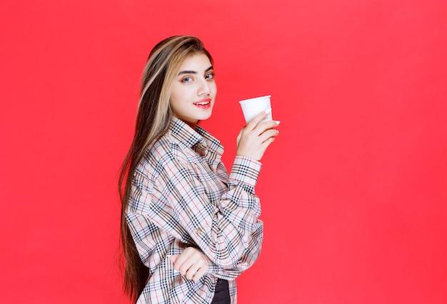 Menina de camisa xadrez segurando uma xícara de café descartável branca