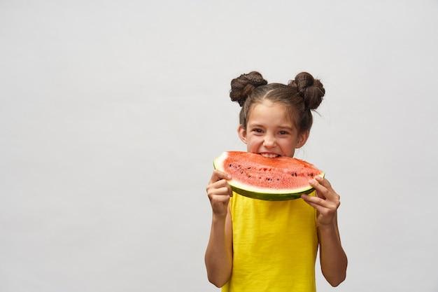Menina de camiseta amarela, rindo alegremente e mordendo a fatia de melancia