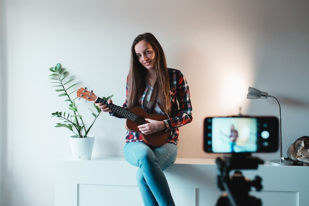 Menina de camiseta e calça jeans escreve um vlog no telefone sobre tocar ukulele.