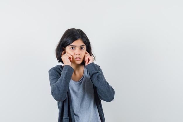 Menina de camiseta e jaqueta tapando as orelhas com os dedos e parecendo confusa