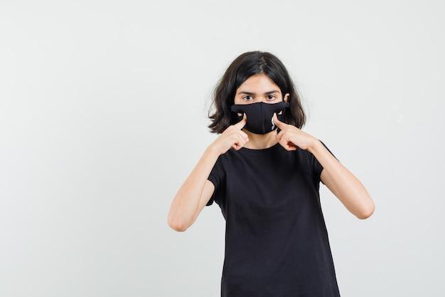 Menina de camiseta preta apontando para a máscara dela e olhando cuidadosa, vista frontal.