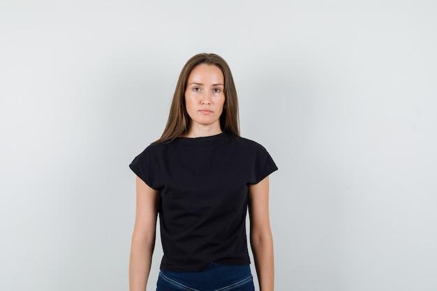 Menina de camiseta preta, calça olhando para a câmera e olhando sério