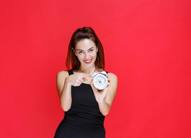 Menina de camiseta preta segurando um despertador
