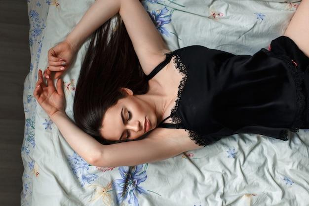 Menina de camisola preta deitada na cama