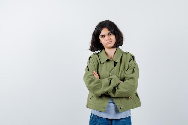 Menina de casaco, camiseta, jeans em pé com os braços cruzados e parecendo confiante, vista frontal.