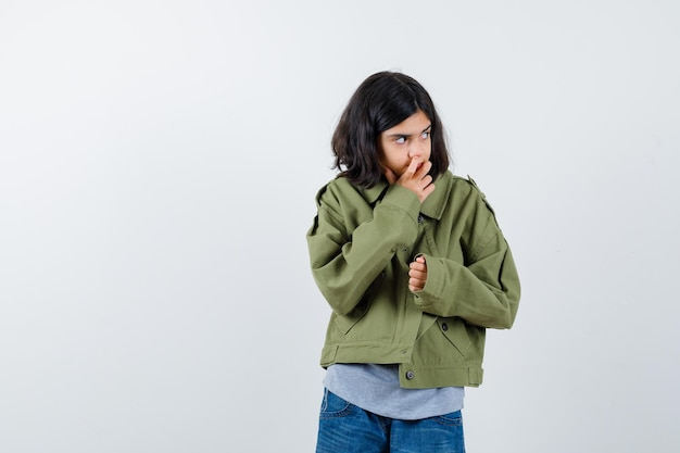Menina de casaco, camiseta, jeans roendo as unhas enquanto olha para longe e parece pensativa, vista frontal.