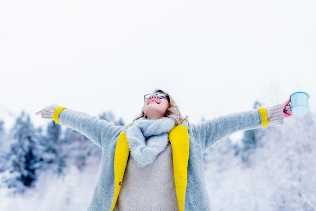 Menina de casaco com copo de bebida em uma floresta de neve
