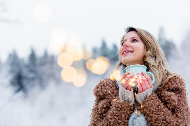 Menina de casaco com copo de bebida quente em uma floresta de neve