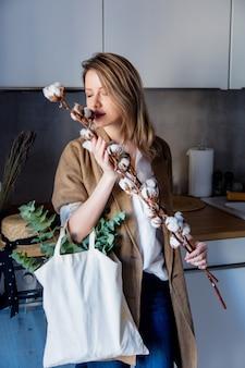 Menina de casaco com sacola e algodão-planta em uma cozinha