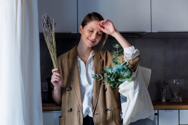 Menina de casaco com sacola e plantas em uma cozinha