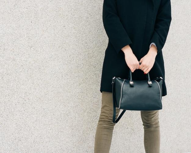 Menina de casaco preto, jeans verde e uma bolsa na mão fica em uma superfície de parede bege