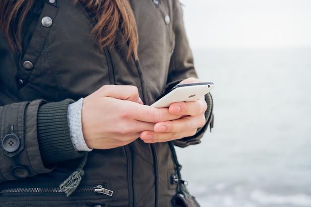 Menina de casaco usa um smartphone enquanto caminhava ao longo da praia