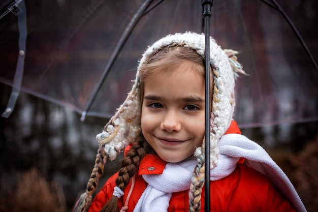 Menina de casaco vermelho com guarda-chuva transparente andando sozinho na floresta de primavera