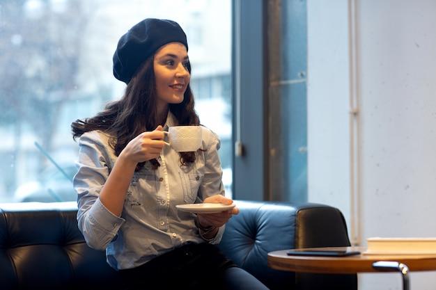 Menina de chapéu bebe café