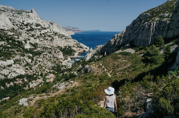Menina de chapéu branco andando no parque nacional de calanques em dia ensolarado. cartão postal de viagem pitoresca.