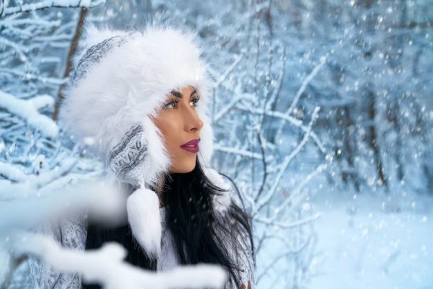 Menina de chapéu branco de inverno na floresta com neve perto de árvores.