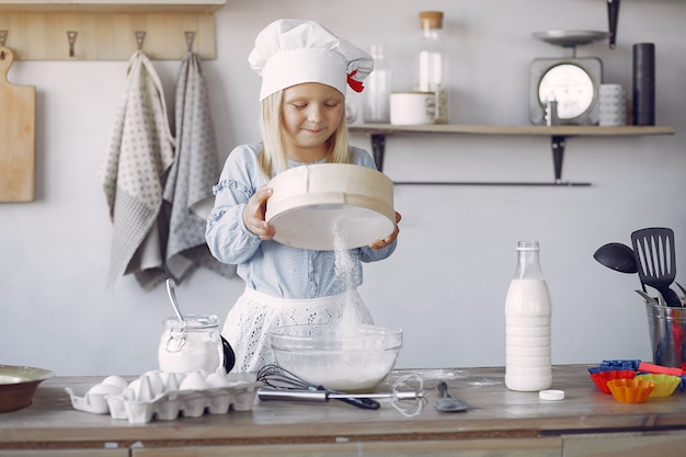 Menina de chapéu branco shef cozinhar a massa para biscoitos