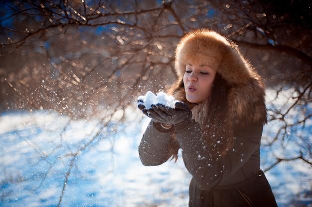 Menina de chapéu com abas de orelha soprando na neve.
