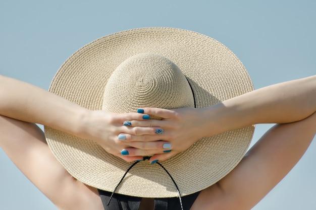 Menina de chapéu com as mãos atrás da cabeça close-up vista de trás