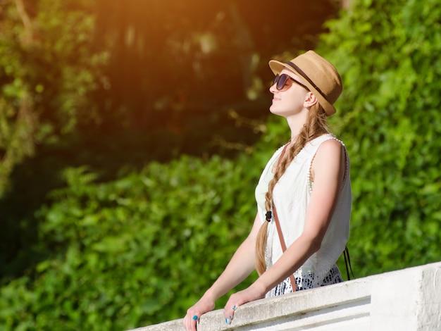 Menina de chapéu com os olhos fechados, curtindo a natureza. dia de sol, parque