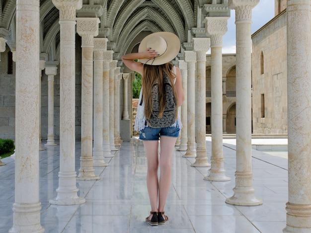 Menina de chapéu com uma mochila em pé entre colunas