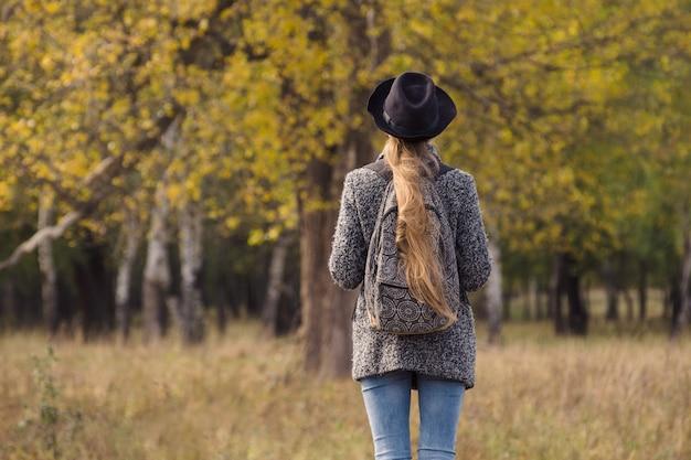 Menina de chapéu com uma mochila em pé na floresta de outono