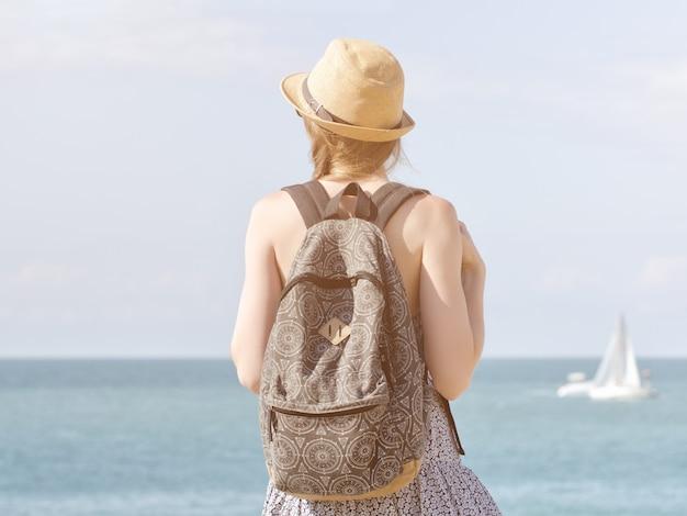 Menina de chapéu com uma mochila em pé no litoral. veleiro à distância. vista traseira