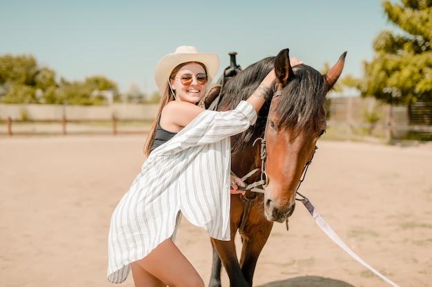 Menina de chapéu de cowboy e camisa andando com um cavalo em uma fazenda