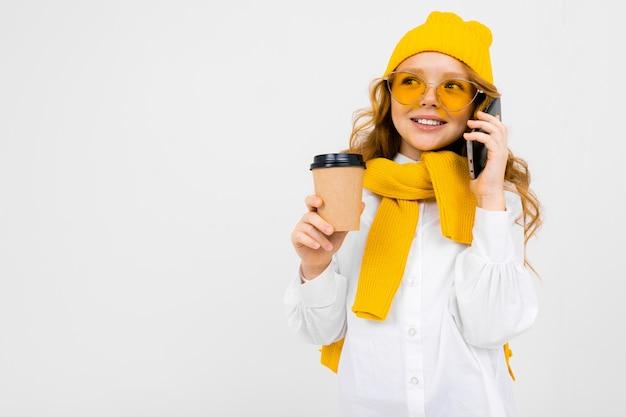 Menina de chapéu de inverno e cachecol com um copo de bebida quente e um smartphone nas mãos em um branco com espaço de cópia