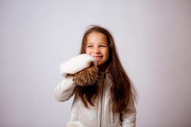 Menina de chapéu de inverno sorrindo em branco
