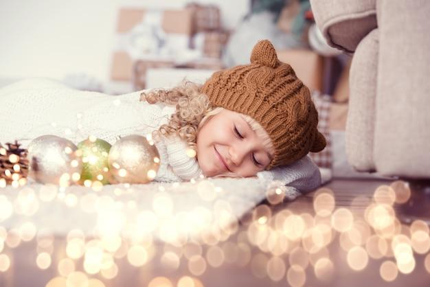 Menina de chapéu de malha perto de árvore de natal faz um desejo para o ano novo.