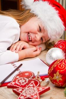 Menina de chapéu de natal escrever carta ao papai noel