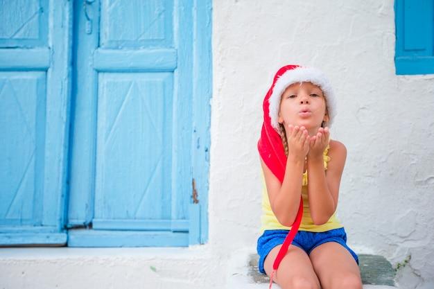 Menina de chapéu de papai noel ao ar livre na rua velha nas férias de natal em mykonos. garoto na rua da típica aldeia tradicional grega manda beijos