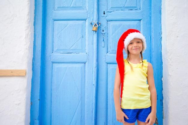 Menina de chapéu de papai noel ao ar livre na rua velha nas férias de natal em mykonos.
