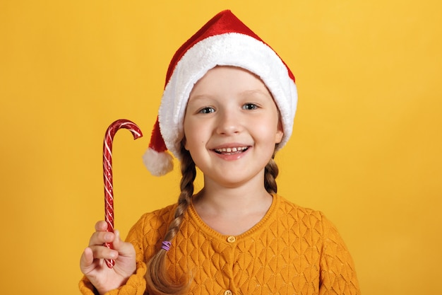 Menina de chapéu de papai noel com doces de natal.