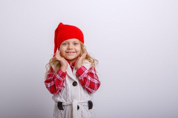 Menina de chapéu de papai noel em fundo cinza