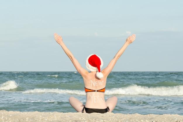 Menina de chapéu de papai noel na costa do mar. mãos levantadas.