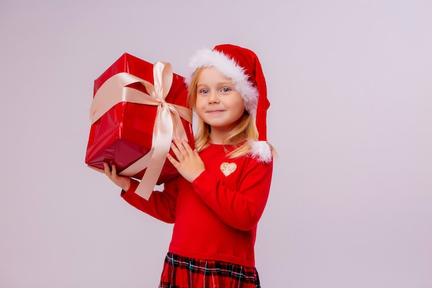 Menina de chapéu de papai noel segurando a caixa de presente vermelha na parede branca