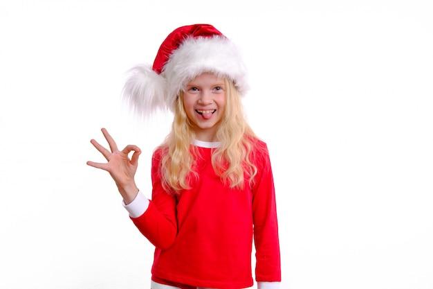 Menina de chapéu de papai noel vermelho natal sorrindo e mostrando bem ok