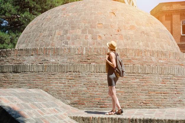Menina de chapéu e com uma mochila em pé perto de uma cúpula de tijolos. dia ensolarado