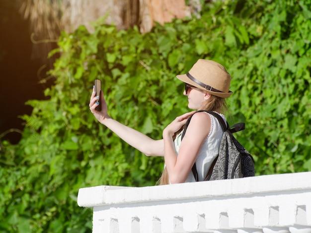 Menina de chapéu e com uma mochila faz selfie no parque