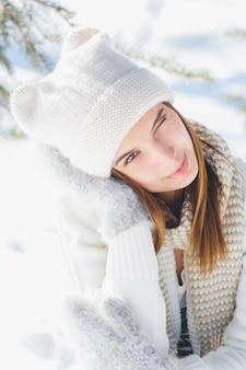 Menina de chapéu e luvas sorrindo no inverno