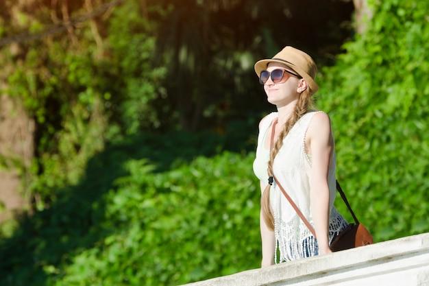 Menina de chapéu e óculos de sol, curtindo a natureza. dia de sol, parque