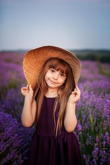 Menina de chapéu em um campo de flores lilás