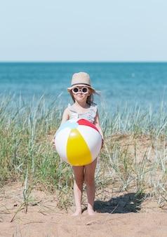 Menina de chapéu jogando na praia com bola, dia ensolarado de verão. conceito de férias