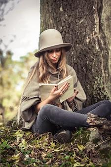 Menina de chapéu, lendo um livro na floresta de outono