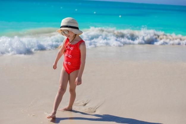 Menina de chapéu na praia durante as férias do caribe
